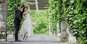 Bride and groom dancing in park.
