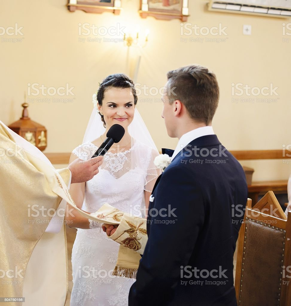 Bride and groom during the wedding ceremony in the church. stock photo