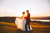 Bride and groom embrace in nature during sunset