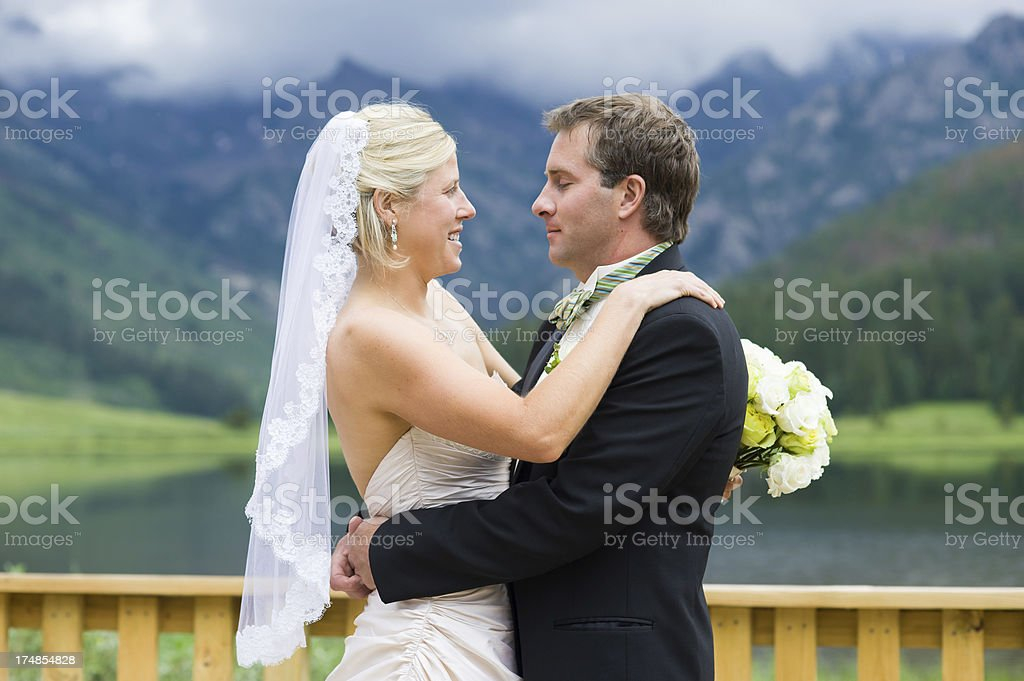 Bride and Groom Embracing at Scenic Lake stock photo
