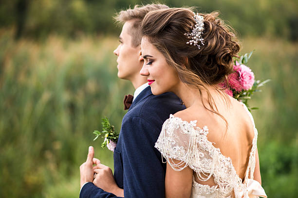 bride and groom embracing in the park - flitterwochen kleid stock-fotos und bilder