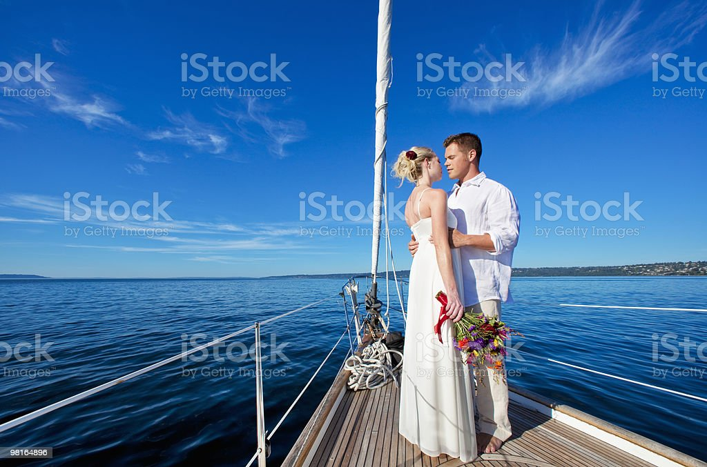 Bride and groom embracing on bow of sailboat royalty-free stock photo