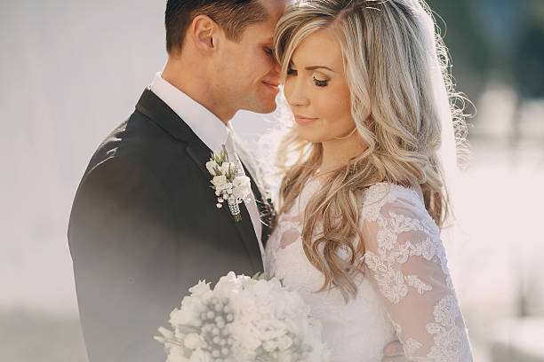 Bride and groom embracing on the wedding day under the sun stock photo