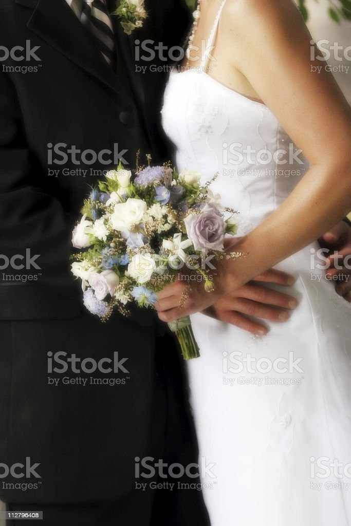 Bride and groom embracing with bouquet royalty-free stock photo