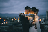 Romantic newlyde couple standing on the roof top in the city in the night