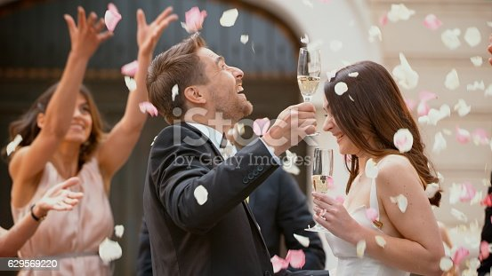 Bride and groom with champagne, friends throwing flower petals over bride and groom.