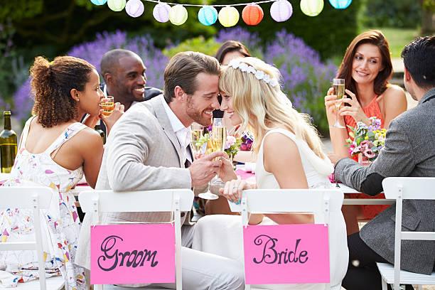 braut und bräutigam genießen eine mahlzeit im hochzeitsempfang - bräutigam tisch stock-fotos und bilder