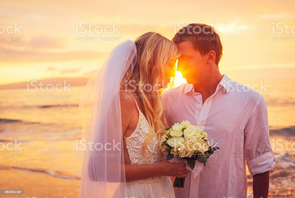 A bride and groom enjoying the view and the amazing sunset stock photo