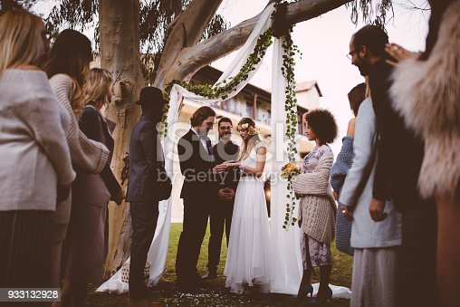 Couple exchanging vows of love and wedding rings at outdoors wedding ceremony with multi-ethnic guests