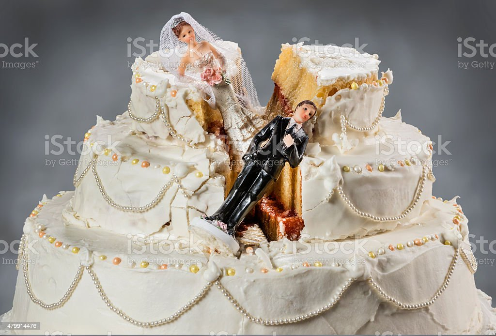 Bride and groom figurines collapsed at ruined wedding cake Spouses always seem to struggle to keep their relationship alive 2015 Stock Photo