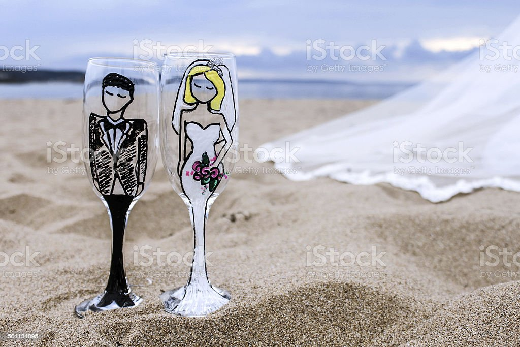Bride and groom glasses with part of wedding dress stock photo
