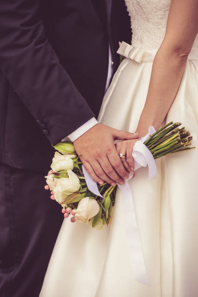 bride and groom hand in hand - diamond ring hand stock photos and pictures