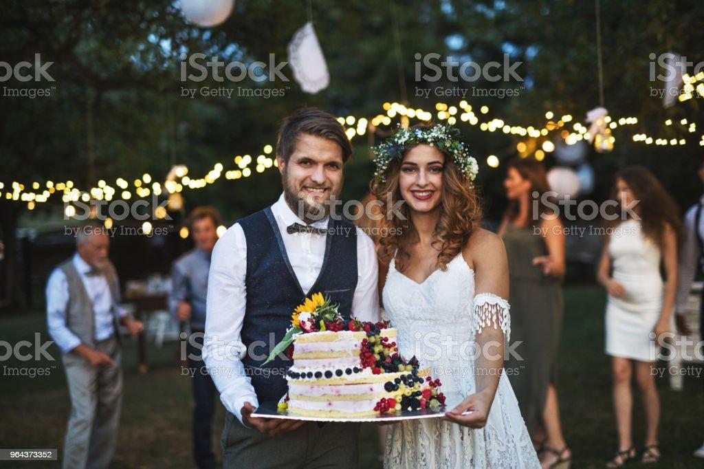Bruid en bruidegom, een taart te houden bij de bruiloft receptie buiten in de achtertuin. - Royalty-free 20-29 jaar Stockfoto