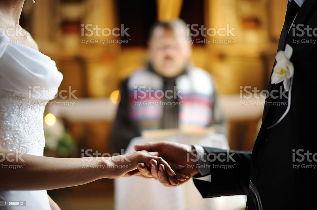 Bride and groom holding each other's hands stock photo