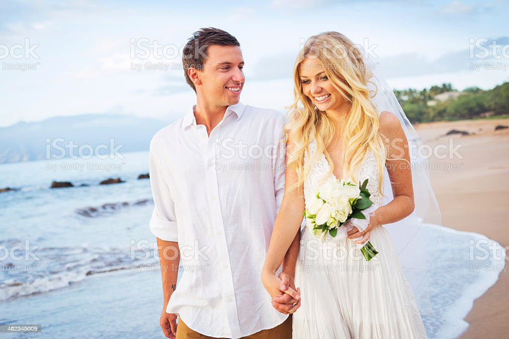 A bride and groom holding hands and walking on a beach stock photo