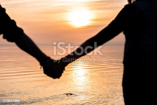 872969580 istock photo Bride and groom holding hands in front of a sunset 470842986