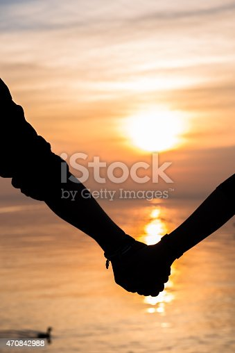 872969580 istock photo Bride and groom holding hands in front of a sunset 470842988