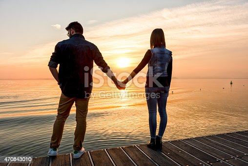 872969580 istock photo Bride and groom holding hands in front of a sunset 470843010