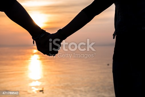 872969580 istock photo Bride and groom holding hands in front of a sunset 471789542