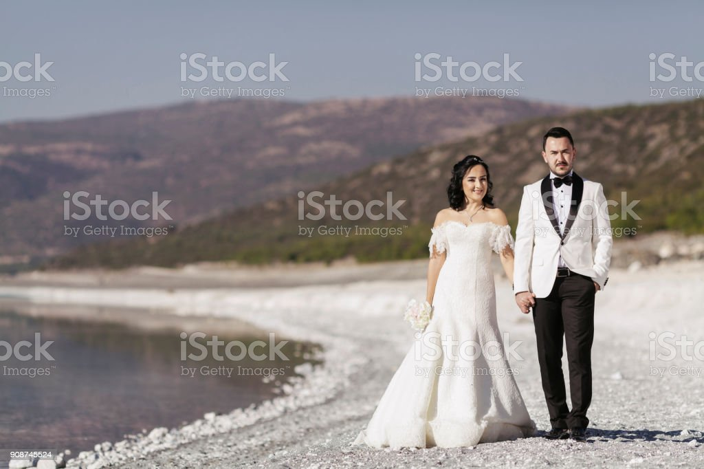 Bride and groom holding hands on the beah posing for camera stock photo