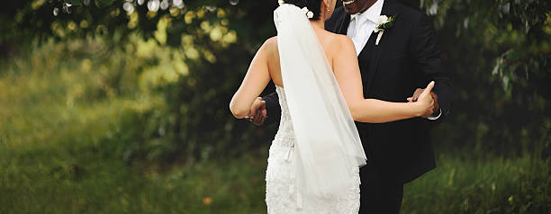 bride and groom holding hands stock photo
