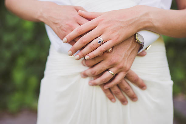 bride and groom holding hands, wedding rings on their fingers - sapphire gemstone stock photos and pictures