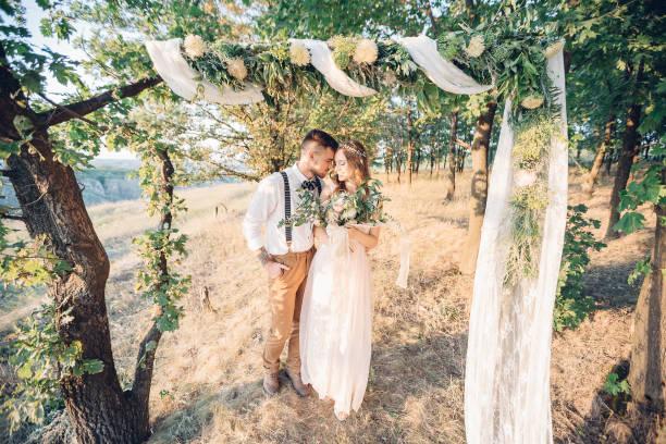 bride and groom hugging at the wedding in nature. - grüne hochzeit themen stock-fotos und bilder