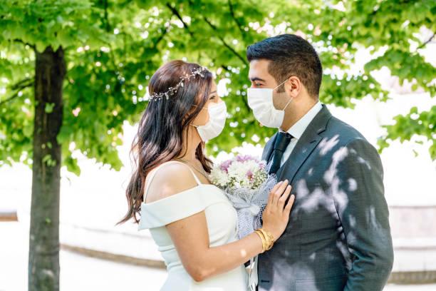 braut und bräutigam in einer gesichtsschutzmaske - hochzeit stock-fotos und bilder