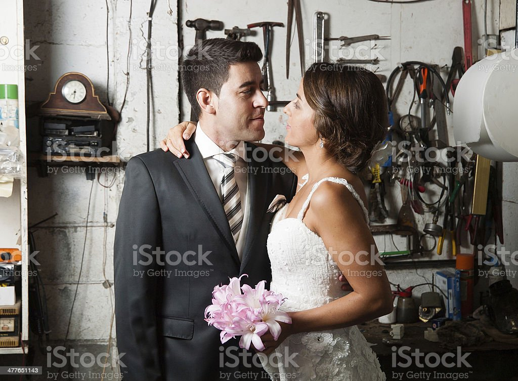 Bride and groom in a garage stock photo