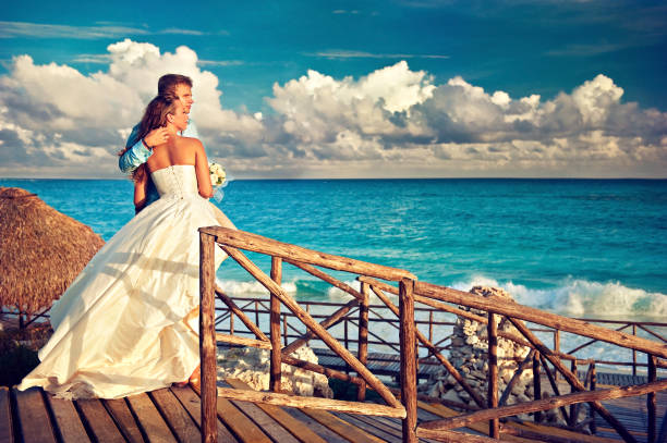 braut und bräutigam in einem umarmungen bleibt vor schönen seenlandschaft. hochzeit am strand. - hochzeitsreise ohne mann stock-fotos und bilder