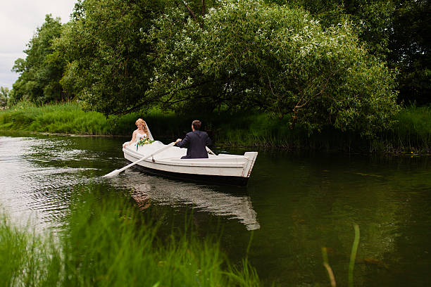 bride and groom in a white boat on the lake stock photo