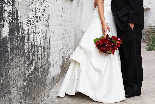 braut und bräutigam im alley, red bouquet - hochzeitskleid in schwarz stock-fotos und bilder