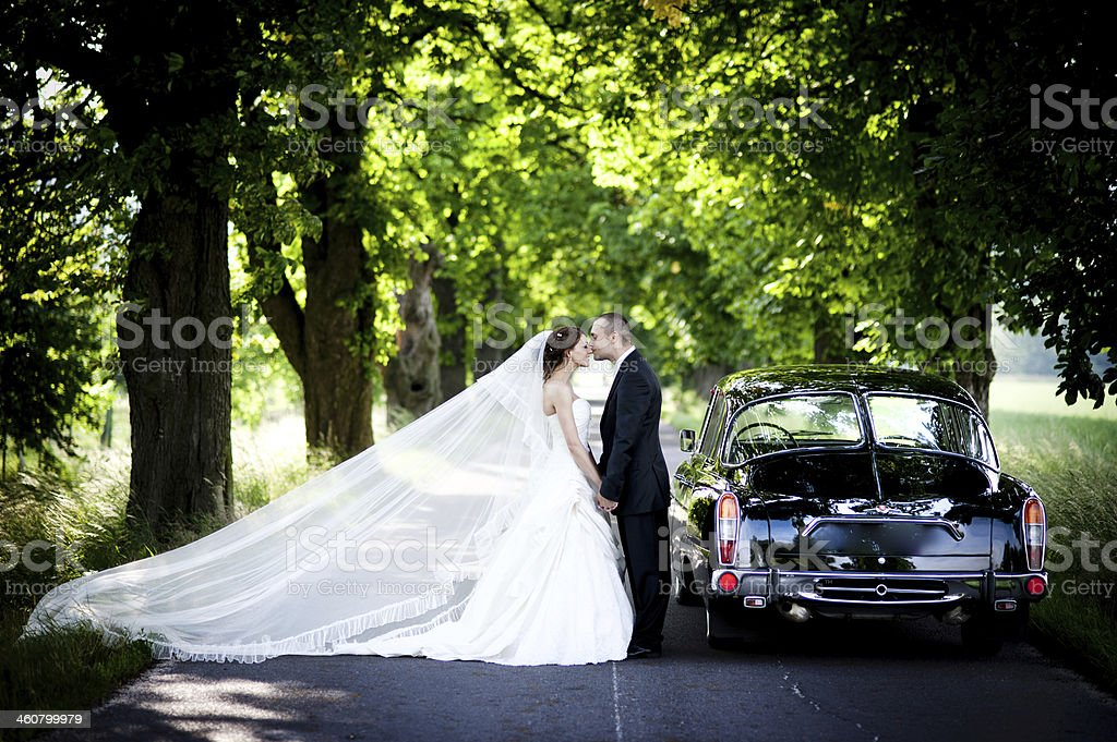 Bride and groom in car stock photo