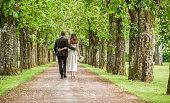 Bride and groom walking in park.