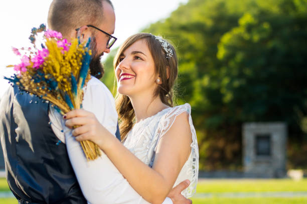 braut und bräutigam in romantischen umarmung bei sonnenuntergang - hipster braut stock-fotos und bilder