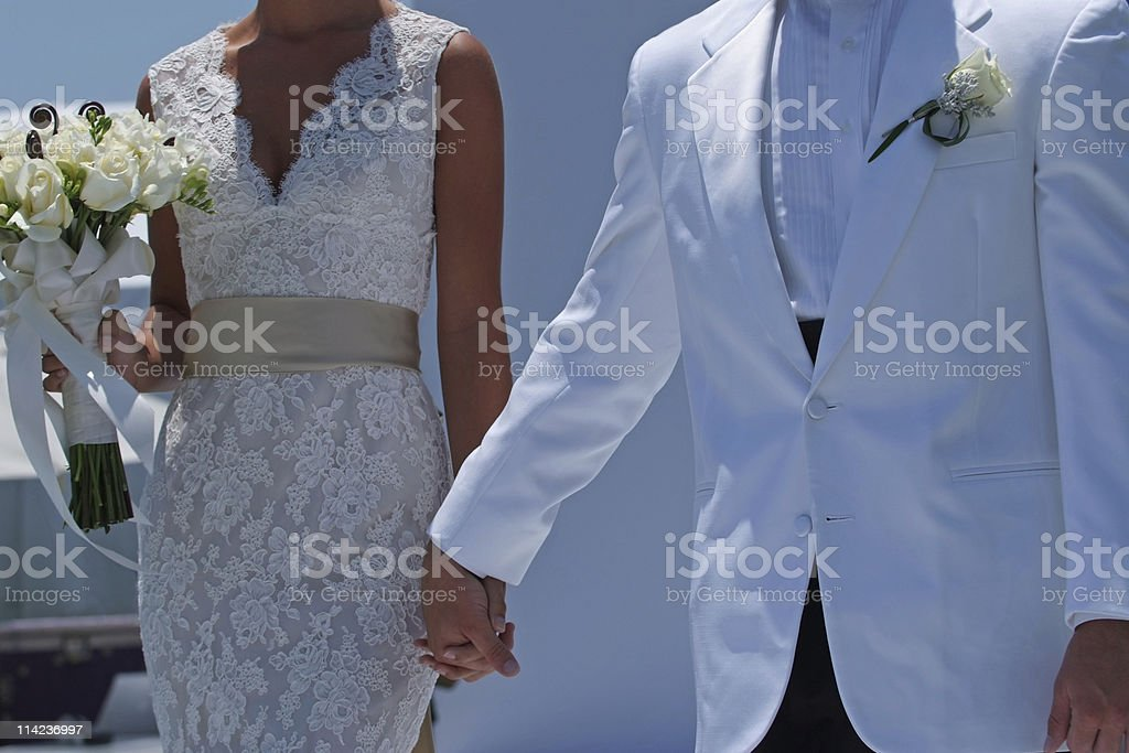 bride and groom in white dresses closing hands royalty-free stock photo