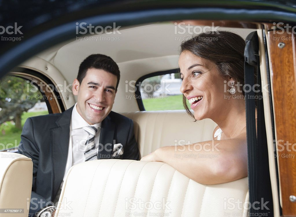 Bride and groom inside a classic car stock photo