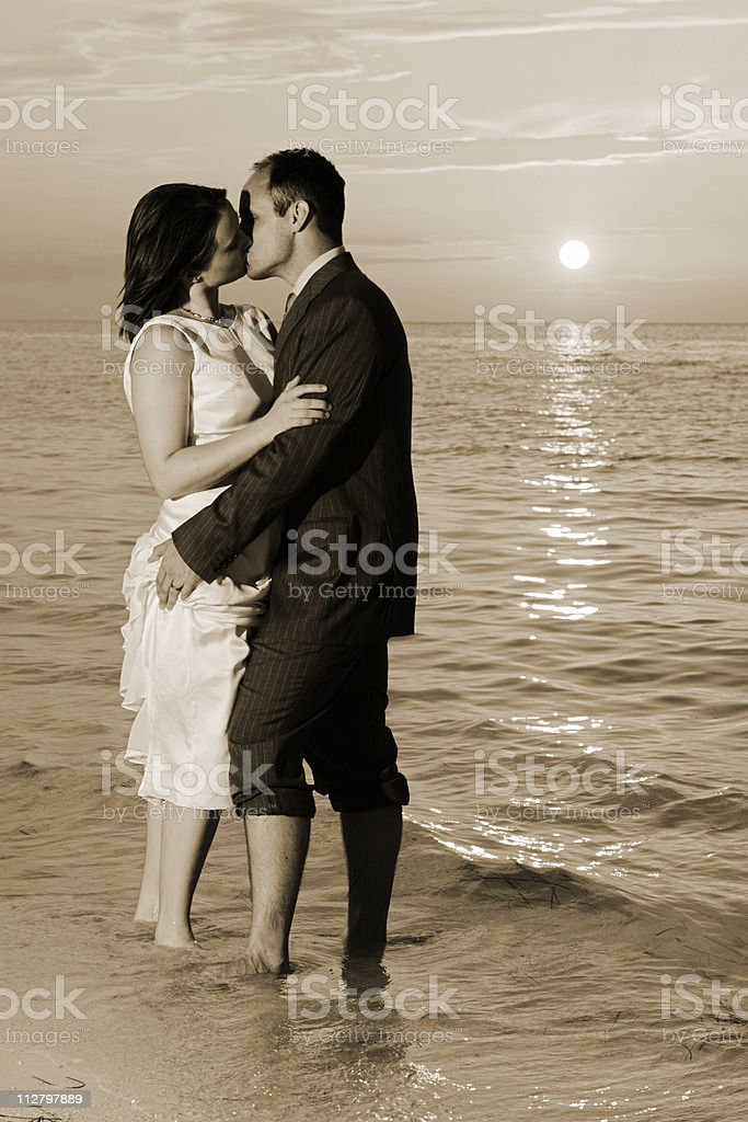 Bride and Groom kiss in the tropical mexico ocean surf royalty-free stock photo