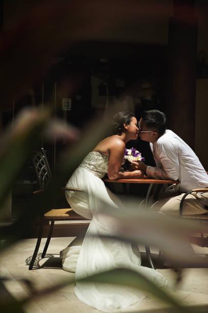 braut und bräutigam küssen im innenhof - hofkleider stock-fotos und bilder