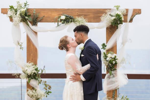 Bride and groom kissing in front of wedding altar A bride and groom embrace and kiss in front of a decorated simple outdoor wedding altar.  They stand on a balcony in front of a scenic view. altar stock pictures, royalty-free photos & images