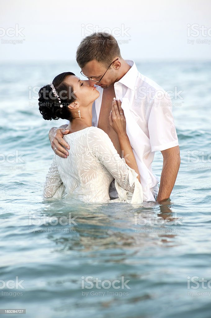 Bride and groom kissing in the water stock photo