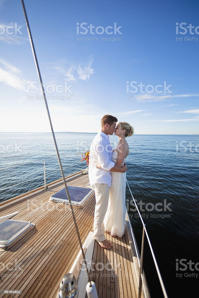 Bride and groom kissing on bow of sailboat royalty-free stock photo