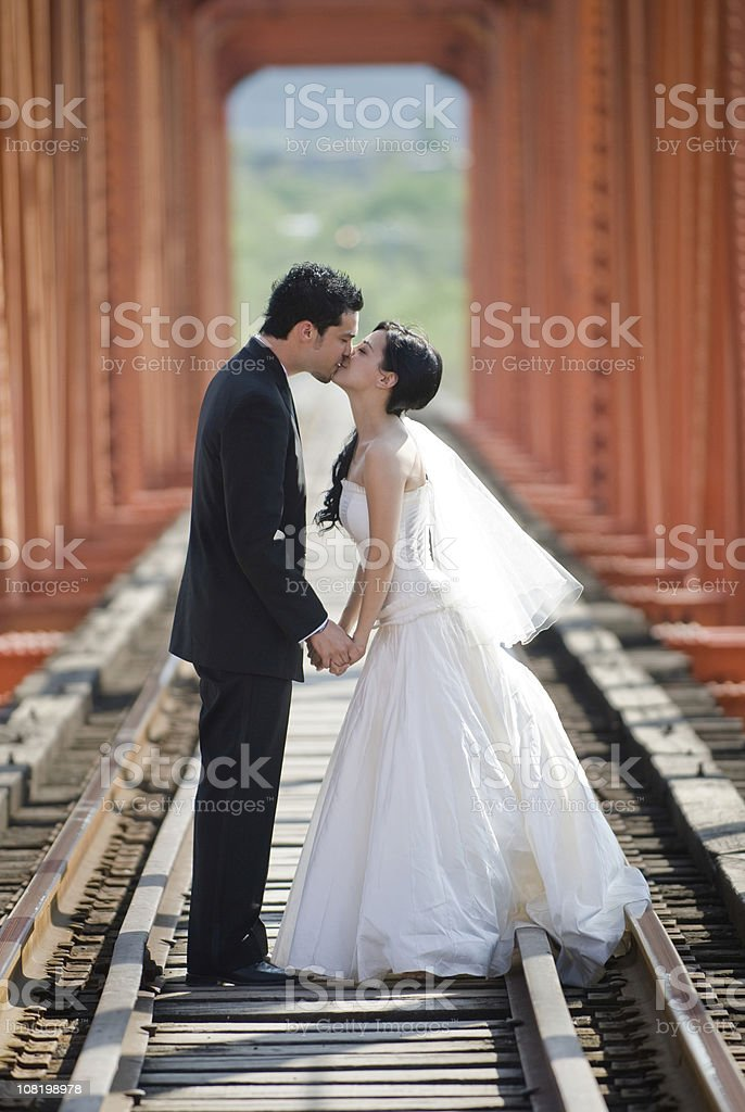 Bride and Groom Kissing on Railroad Track Bridge royalty-free stock photo