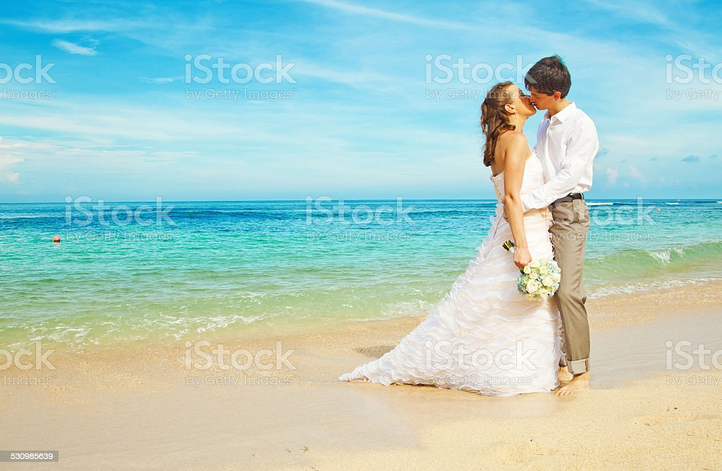 Bride and groom kissing on the beach stock photo