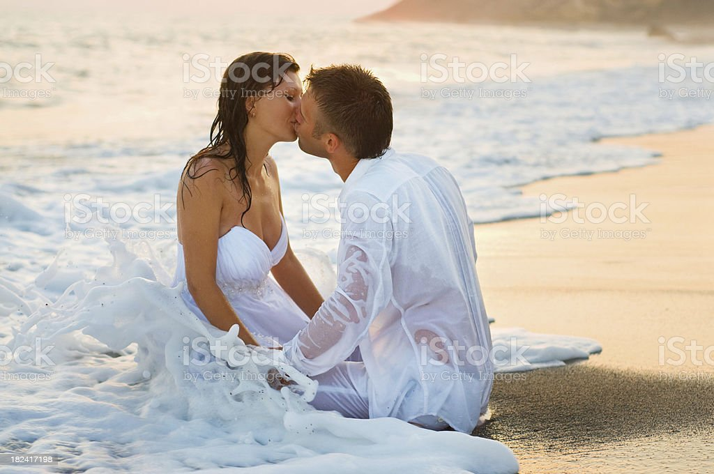 Bride and groom sitting and kissing on the beautiful beach with...