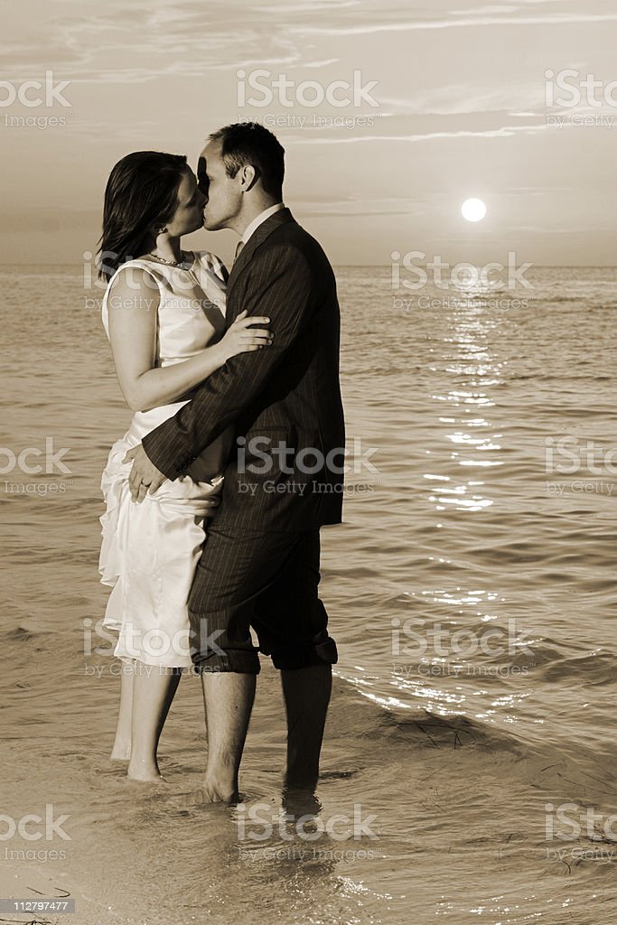 Bride and Groom Kissing on Tropical Beach at Sunset royalty-free stock photo
