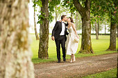Bride holding bouquet and kissing to groom while walking on single track in park.