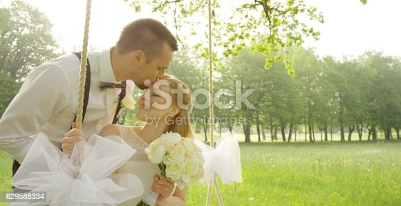 Groom kissing bride on her forehead while sitting on swing in park.