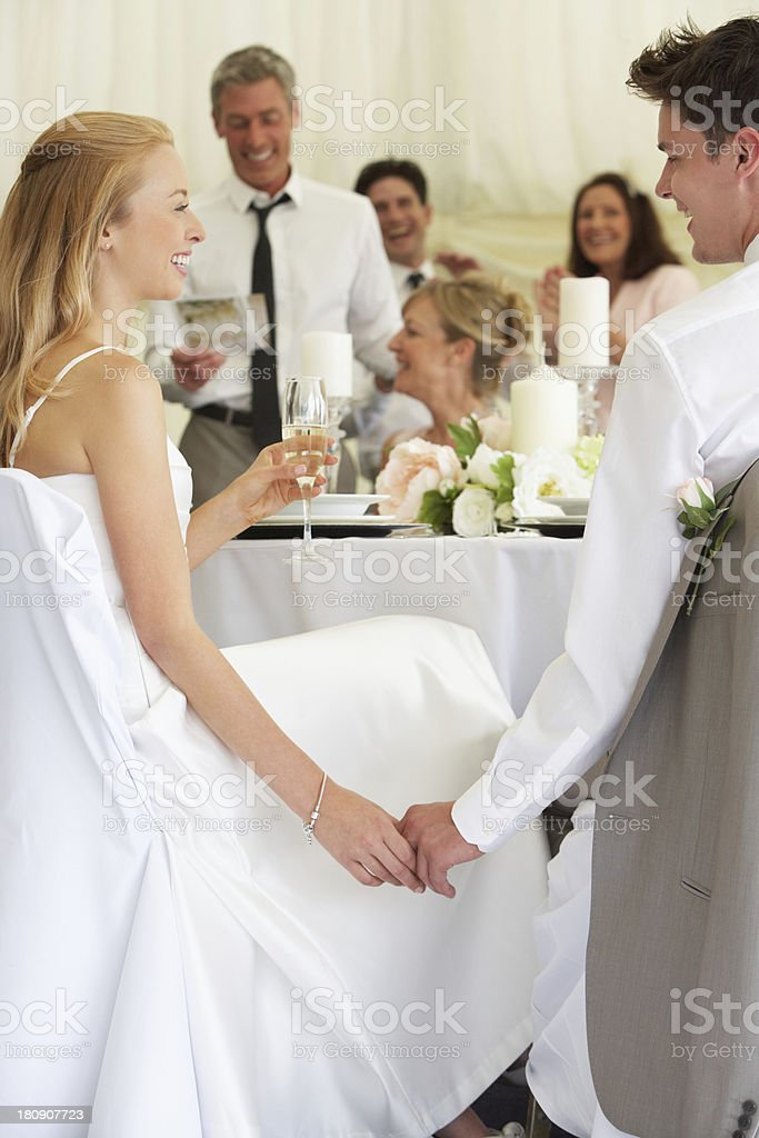 Bride And Groom Listening To Speeches At Reception stock photo