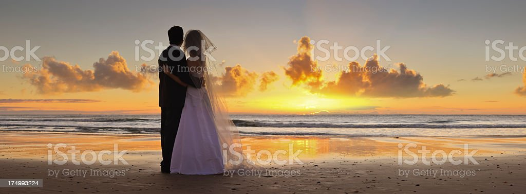 Bride and groom looking towards sunset on beach stock photo